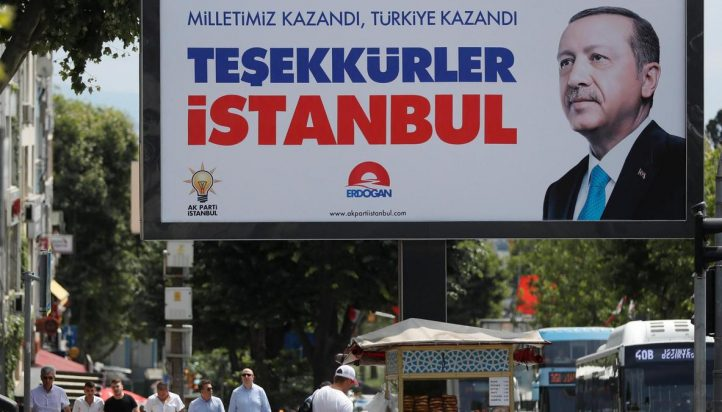 People walk past a poster for Turkey's President Tayyip Erdogan in Istanbul, Turkey, June 25, 2018. The poster reads: 'Our people won, Turkey won, Thank you istanbul'. Osman Orsal / Reuters Photo